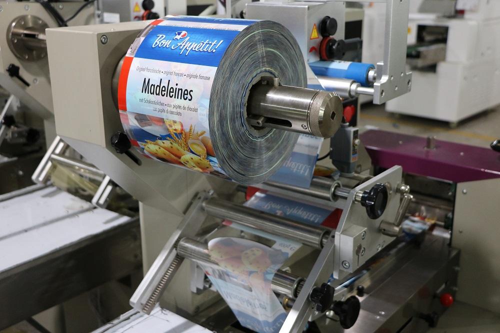 Cách thức hoạt động của thiết bị:  Băng tải hoạt động: Là chìa khóa cơ khí trong bộ phận của thiết được làm bằng thép không gỉ, phù hợp với thực phẩm QS. Bảng tải truyền mọi hoạt động từ khâu đóng gói xúc xích đến với nhân công để sắp xếp phù hợp bỏ vào thùng  Thiết bị làm phồng túi: Tự động cuộn phim hình thành hình dạng túi, linh hoạt trong sản xuất với các dạng kích thước khác nhau và thuận tiện cho cơ sở là không cần điều chỉnh quá nhiều lần cho các sản phẩm khác nhau nên tiết kiệm được thời gian  Màn hình cảm ứng: Được cài đặt với nhiều ngôn ngữ khác nhau nên có thể điều chỉnh sao cho phù hợp môi trường làm việc của bạn. Màn hình cảm ứng với kích thước lớn nên dễ dàng cài đặt, hiện thị rõ các thông số và có thể dừng mọi hoạt động chỉ với một nút bấm  Dao cắt và niêm phong sản phẩm: Bộ phận dao hoạt động liên tục để cắt sản phẩm sao cho đúng vị trí  Định hình vị trí: Sử dụng bên ngoài phim vị trí cấu trúc, bao bì phim cài đặt là đơn giản hơn và một cách nhanh chóng hơn cho việc sản xuất