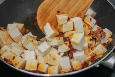 Cách làm đậu hũ Tứ Xuyên: Sơ chế nguyên vật liệu: Nấm rơm, bỏ gốc ngâm trong nước muối pha loãng trong 5 – 10 phút để loại bỏ các chất dơ và bụi bẩn. Sau đó, bạn vớt ra ngâm vào nước nóng 3 phút rồi cắt nhỏ, sao cho vừa ăn. Đừng cắt quá nhỏ vì lúc xào sẽ làm nát nấm Hành tím, tỏi băm nhuyễn hoặc ta có thể mua sẵn ngoài chợ đem về sử dụng Hành lá, ớt sau khi mua về rửa sạch. Sau đó, đem đầu hành băm nhỏ. Phần lá cắt nhỏ. Ớt sừng bỏ hạt, băm nhỏ. Tôm lột bỏ vỏ, lấy chỉ đen, rửa sạch, đập dập, băm nhuyễn. Ướp vào 1 ít tiêu. Có thể đem theo ít gia vị Thịt nạc băm nhỏ, ướp vào 2 muỗng cà phê gốc hành lá, ½ muỗng cà phê hạt nêm. Đậu hũ non cắt thành những khối vuông vừa ăn. Hoa tiêu giã mịn. Hòa tan 15g bột năng và 15g bột bắp với 45ml nước. Cách làm nước xốt đậu hủ Tứ Xuyên: Bắc chảo lên bếp, cho vào 1 muỗng canh dầu ăn, phi thơm hành tím, tỏi. Khi hành tỏi đã vàng, bạn cho thịt, tôm vào xào săn lại rồi tiếp tục cho nấm, 50g đậu tương cay, 20g dầu hào, 1 muỗng canh đường, 5g ớt bột, ớt băm và 400ml nước, đun sôi tất cả lên. Bạn có thể nêm nếm lại cho vừa ăn theo khẩu vị của mình. Khi hỗn hợp sôi được 2 phút, bạn từ từ cho bột năng vào đến khi hỗn hợp sệt lại vừa phải (không cần sử dụng hết số bột năng đã pha). Tiếp tục, bạn cho 30g rượu hoa tiêu vào. Xào Xốt và thành phẩm đậu hũ Tứ Xuyên: Bạn cho đậu hũ vào chảo xốt đun cho sôi lại trong khoảng 3 – 5 phút. Trong quá trình đun, bạn đảo nhẹ tay để đậu hũ không bị nát và thấm gia vị. Cuối cùng cho hoa tiêu vào, tắt bếp. Trước khi ăn, bạn cho vào 1 muỗng canh dầu mè, hành lá.