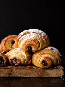 """Pain Au Chocolat – được mệnh danh người anh em của bánh Croissant Pain au chocolat hay còn được gọi là bánh mì socola – 1 trong 7 món ngon Paris dành cho người hảo ngọt. Không ai biết nguồn gốc cụ thể của chiếc bánh này, nhưng tất cả đều chắc chắn rằng việc cho chocolate vào công thức làm bánh này là """"một tai nạn tuyệt vời"""". Lớp vỏ giòn xốp thơm ngậy, lại có thêm hương vị socola đắng đắng ngọt ngọt nồng nàn bên trong, khiến ai đã nếm một lần đều nhớ mãi không quên. Có khả năng nói người Pháp chính là bậc thầy trong việc biến những món ăn tưởng chừng giản đơn trở thành hấp dẫn và xinh xắn hơn rất nhiều. Và bánh Pain Au Chocolat chính là một trong những số đó. Bánh được làm từ bột mì, sữa tươi, bơ, trứng, ngặt nghèo lớp phủ chocolate vô cùng đơn giản tuy nhiên lại đẹp mắt và mang lại hương vị ngọt ngào khó cưỡng. nếu như là một người hảo ngọt thì bạn không nên bỏ qua loại bánh này đâu. Nguyên liệu làm bánh: Phần vỏ bánh: 60 gram bơ nhạt, để ở nhiệt độ phòng 500 gram bột mì đa dụng 50 gram đường 2 thìa cà phê muối 9.3 gram men instant 360ml sữa bò nguyên kem 115 gram socola đắng vừa, thái nhỏ Đường bột trang trí (tùy chọn) Phần bơ: 345 gram bơ nhạt, để ở nhiệt độ phòng 16 gram bột mì đa dụng Phần trứng phết lên Pain au Chocolat: 1 quả trứng 30ml sữa bò nguyên kem Cách làm gồm các bước sau đây: Bước 1: Chia 60 gram bơ ra làm 4 phần, cho vào tô cùng bột mì, đường, muối và men. Trộn đều bằng máy trộn ở tốc độ trung bình thấp. Đổ từ từ 360ml sữa vào hỗn hợp. Khi đã cho hết sữa vào, tăng tốc độ đánh lên trung bình hoặc nhồi bằng tay trong tối thiểu 5 phút. Khi quan sát thấy bột gần như tách khỏi thành tô và đàn hồi lại khi nhấn ngón tay vào là thành công. Bước 2:Phủ bột đều lên tay và mặt khay, lấy bột ra khỏi tô và nhồi thành hình tròn. Sau đó, bọc lại bằng màng bọc thực phẩm hoặc giấy bạc. Cho vào ngăn mát tủ lạnh và để bột nghỉ trong 30 phút. Bước 3:Lấy bột ra khỏi tủ lạnh và dàn phẳng bột bằng tay, sao cho phần bột thành hình tứ giác có kích thước 25x35cm. Đừng lo lắng """