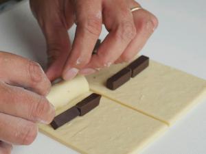 """Pain Au Chocolat – được mệnh danh người anh em của bánh Croissant  Pain au chocolat hay còn được gọi là bánh mì socola – 1 trong 7 món ngon Paris dành cho người hảo ngọt. Không ai biết nguồn gốc cụ thể của chiếc bánh này, nhưng tất cả đều chắc chắn rằng việc cho chocolate vào công thức làm bánh này là """"một tai nạn tuyệt vời"""".  Lớp vỏ giòn xốp thơm ngậy, lại có thêm hương vị socola đắng đắng ngọt ngọt nồng nàn bên trong, khiến ai đã nếm một lần đều nhớ mãi không quên.  Có khả năng nói người Pháp chính là bậc thầy trong việc biến những món ăn tưởng chừng giản đơn trở thành hấp dẫn và xinh xắn hơn rất nhiều. Và bánh Pain Au Chocolat chính là một trong những số đó. Bánh được làm từ bột mì, sữa tươi, bơ, trứng, ngặt nghèo lớp phủ chocolate vô cùng đơn giản tuy nhiên lại đẹp mắt và mang lại hương vị ngọt ngào khó cưỡng. nếu như là một người hảo ngọt thì bạn không nên bỏ qua loại bánh này đâu.  Nguyên liệu làm bánh: Phần vỏ bánh: 60 gram bơ nhạt, để ở nhiệt độ phòng 500 gram bột mì đa dụng 50 gram đường 2 thìa cà phê muối 9.3 gram men instant 360ml sữa bò nguyên kem 115 gram socola đắng vừa, thái nhỏ Đường bột trang trí (tùy chọn) Phần bơ: 345 gram bơ nhạt, để ở nhiệt độ phòng 16 gram bột mì đa dụng Phần trứng phết lên Pain au Chocolat: 1 quả trứng 30ml sữa bò nguyên kem Cách làm gồm các bước sau đây:  Bước 1:  Chia 60 gram bơ ra làm 4 phần, cho vào tô cùng bột mì, đường, muối và men. Trộn đều bằng máy trộn ở tốc độ trung bình thấp. Đổ từ từ 360ml sữa vào hỗn hợp. Khi đã cho hết sữa vào, tăng tốc độ đánh lên trung bình hoặc nhồi bằng tay trong tối thiểu 5 phút.  Khi quan sát thấy bột gần như tách khỏi thành tô và đàn hồi lại khi nhấn ngón tay vào là thành công.  Bước 2:Phủ bột đều lên tay và mặt khay, lấy bột ra khỏi tô và nhồi thành hình tròn. Sau đó, bọc lại bằng màng bọc thực phẩm hoặc giấy bạc. Cho vào ngăn mát tủ lạnh và để bột nghỉ trong 30 phút.  Bước 3:Lấy bột ra khỏi tủ lạnh và dàn phẳng bột bằng tay, sao cho phần bột thành hình tứ giác có kích thước 25x35cm. Đừng"""