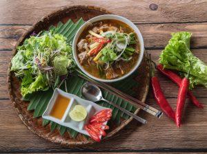 """Bún bò Huế là một trong những đặc sản của xứ Huế, mặc dù món bún này phổ biến trên cả ba miền ở Việt Nam và ở nước ngoài. Tại Huế, món này được gọi đơn giản là """"bún bò"""" hoặc gọi cụ thể hơn là """"bún bò giò heo"""". Các địa phương khác gọi là """"bún bò Huế"""", """"bún bò gốc Huế"""" để chỉ xuất xứ của món ăn này. Món ăn có nguyên liệu chính là bún, thịt bắp bò, giò heo, cùng nước dùng có màu đỏ đặc trưng và vị sả và ruốc. Đôi khi tô bún còn được thêm vào thịt bò tái, chả cua, .... các loại nguyên liệu khác tùy theo sở thích của người nấu và tùy thuộc vào mỗi vùng miền khác nhau cách nêm nếm sẽ khác nhau để cho phù hợp cách ăn nơi đó. Ở xứ Huế, người ta có cách nêm nước dùng rất riêng biệt như thường nêm vào một ít mắm ruốc, góp phần làm nên hương vị rất riêng của nồi bún bò Huế. Sau khi xương bò được hầm chín tới, người ta thường thêm vào một ít chả heo hay chả cua được quết nhuyễn. Thịt bò có thể được cắt mỏng, nhúng vào nước dùng đang sôi trước khi cho vào tô bún (gọi là thịt bò tái). Người ta cũng thường cho thêm một ít ớt bột và gia vị vào tô bún rồi ăn với rau sống gồm giá, rau thơm, xà lách, rau cải con, bắp chuối cắt nhỏ. Nguyên liệu nấu bún bò Huế, ta có gì: Sợi bún bò 500gr bắp bò 500gr xương heo hoặc xương bò Chả Huế 3 muỗng mắm ruốc Chả cua Sả, gừng, tỏi, hành tím, ớt bột Thảo quả, hoa hồi, thanh quế 1 củ hành tây Hạt màu điều Chanh, ớt, hành lá, rau răm Các loại rau sống ăn kèm: Giá, xà lách, Húng quế, tía tô, bắp chuối bào, rau muống bào,… Gia vị: Hạt nêm, muối, nước mắm, bột ngọt, đường, dầu ăn,…. Cách nấu bún bò Huế: Bước 1: Sơ chế nguyên liệu – Rửa sạch xương, rồi trụng sơ qua với nước sôi để loại bỏ chất dơ, nồi nước dùng sẽ trong hơn sau khi nấu. – Gừng, hành tím làm sạch vỏ, sau đó cho vào trong giấy bạc với hoa hồi và quế, đem đi nướng ở trong lò 7 phút ở nhiệt độ 180 độ C. – Sả rửa sạch, đập dập rồi cắt thành từng khúc khoảng 5cm. – Hành tây lột vỏ, rửa sạch, rồi cắt thành từng lát mỏng, sau đó cho vào trong tô nước đá lạnh, ngâm trong 5 – 10 phút để giảm bớt m"""